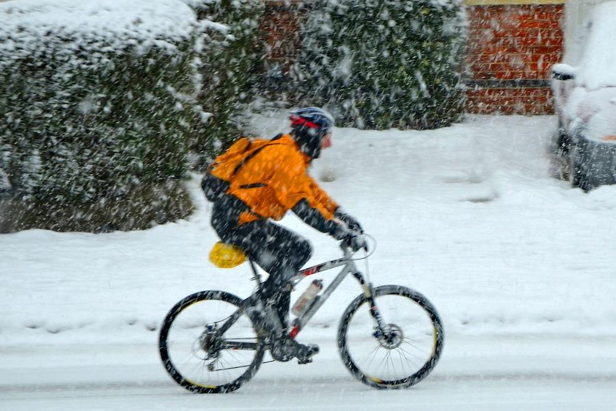 Homem a andar de bicicleta ao frio e com neve