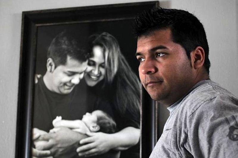 Erick Muñoz junto a um quadro com Marlise e o filho de 15 meses