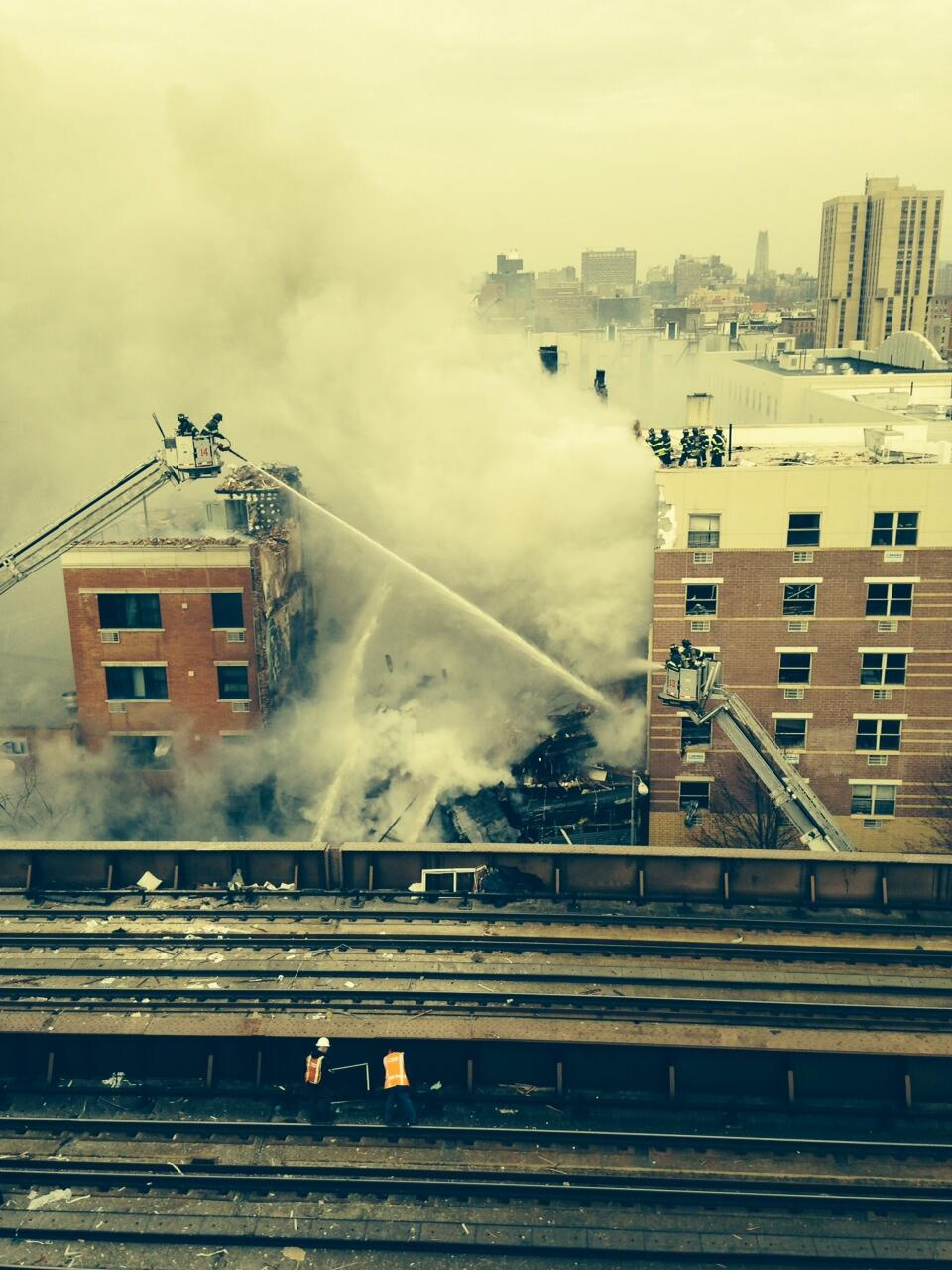 Bombeiros cobatem o fogo em prédio em Nova Iorque que ruiu após explosão