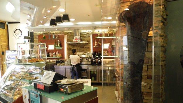 Um café na Lourinhã com um enorme osso de perna de dinossauro ao lado de um balcão de doces.
