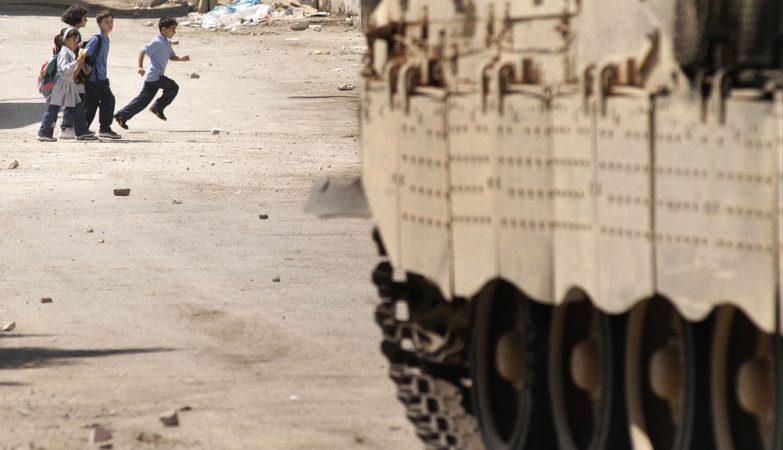 Crianças correm à frente de um tanque israelita em Nablus, na Palestina