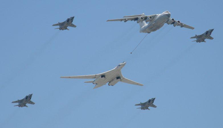 Um avião de reabastecimento Ilyushin Il-78 reabastece um bombardeiro Tupolev Tu-160, escoltados por 4 caças Micoyan&Gurevich MiG-31