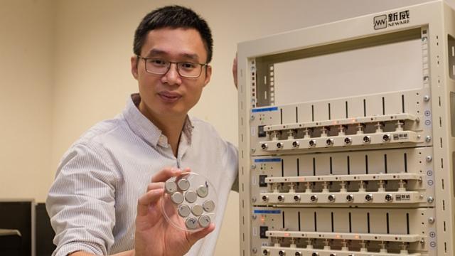 Chen Xiaodong, investigador da Universidade Tecnológica de Nanyang, em Singapura, com as suaspilhas na mão direita e a estação de testes de carga à esquerda.