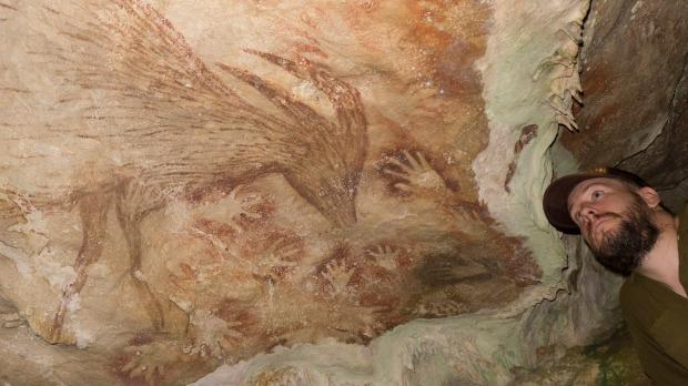 O arqueólogo Maxime Aubert junto à representação de um porco-veado fêmea, pintado numa caverna, na ilha de Sulawesi, na Indonésia