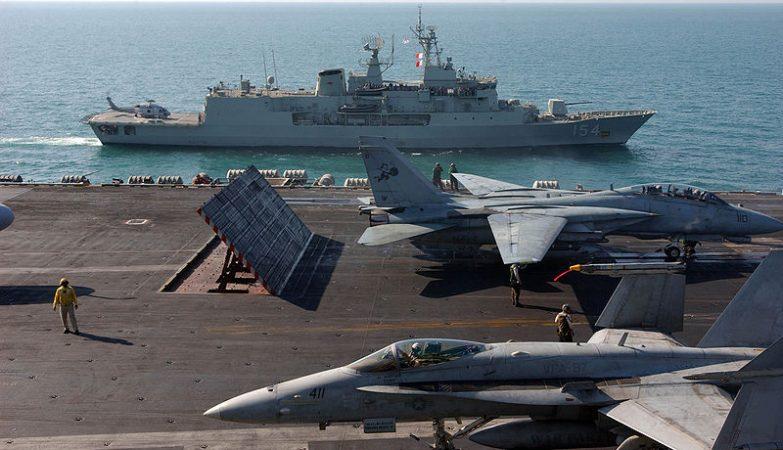 A fragata HMAS Parramatta, da Marinha Real Australiana, ao fundo, ao lado do porta-aviões da marinha norte-americana USS Theodore Roosevelt