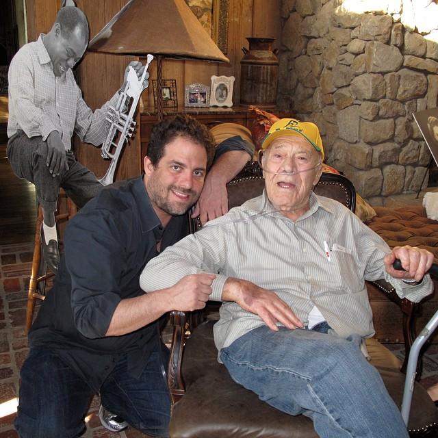 Brett Ratner com Phil Stern, no seu 90º aniversário. Por trás, cardboard com uma das icónicas fotografias de Ster, retratando Loius Armstrong