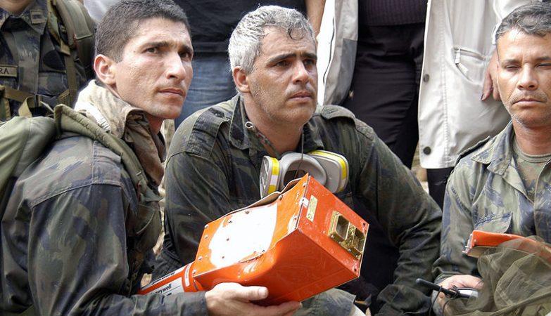 """Militares brasileiros com a caixa-preta do Boeing 737-800 da GOL que caiu em Mato Grosso em setembro de 2006. A """"caixa-preta"""" na realidade é laranja, para facilitar a sua recuperação."""