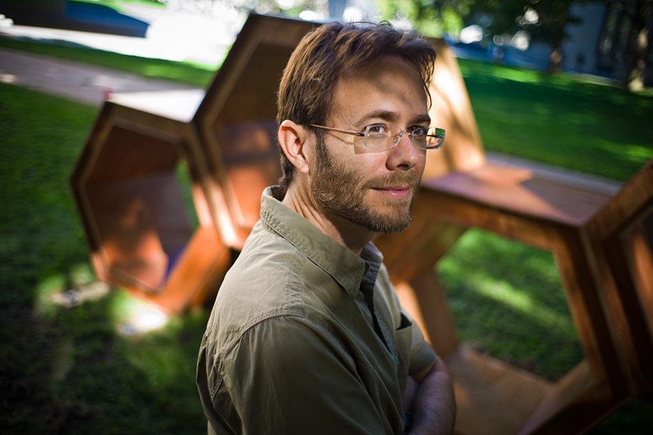 """Bradford Skow, professor de Filosofia do MIT, em frente a """"The Hexagons,"""" escultura de Tara Ebsworth no campus da Universidade."""