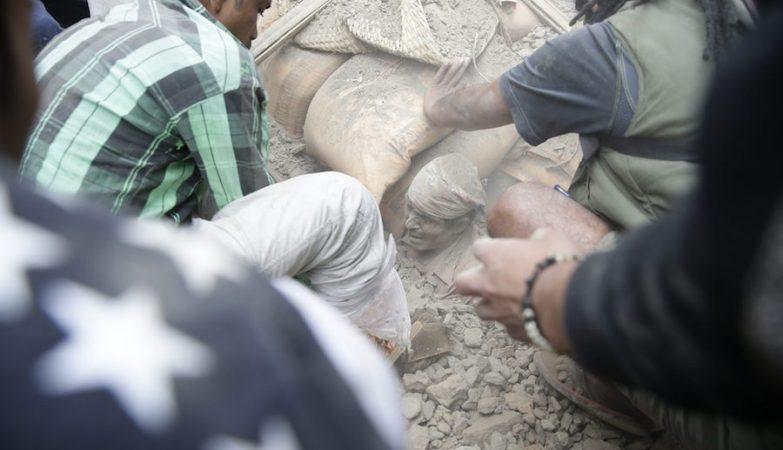 Populares em Katmandu tentam resgatar um homem dos escombros do sismo que atingiu o Nepal