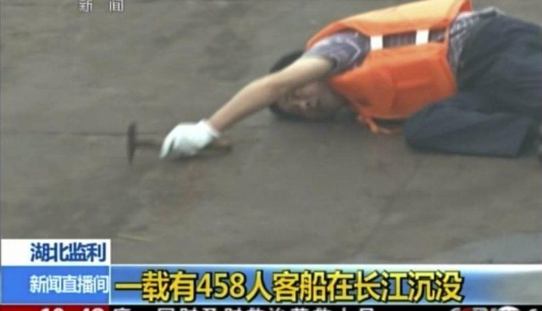 Imagem da China Central Television mostra membro da equipa de resgate a tentar localizar a fonte dos barulhos de possíveis sobreviventes dentro do navio