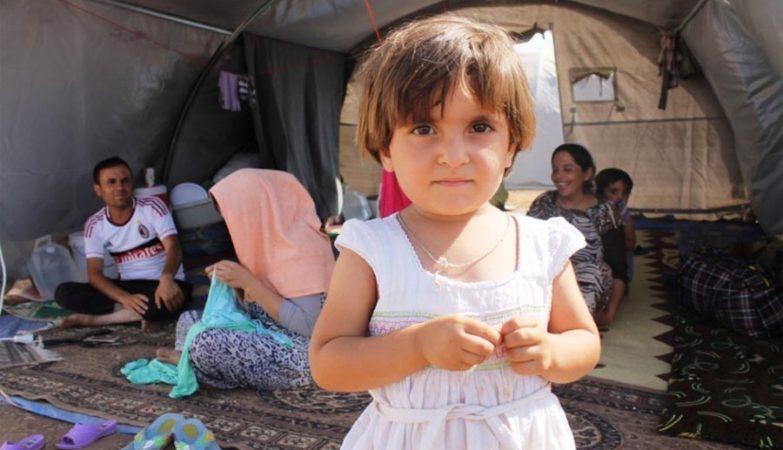 Menina iraquiana com a família no campo de refugiados de Newroz
