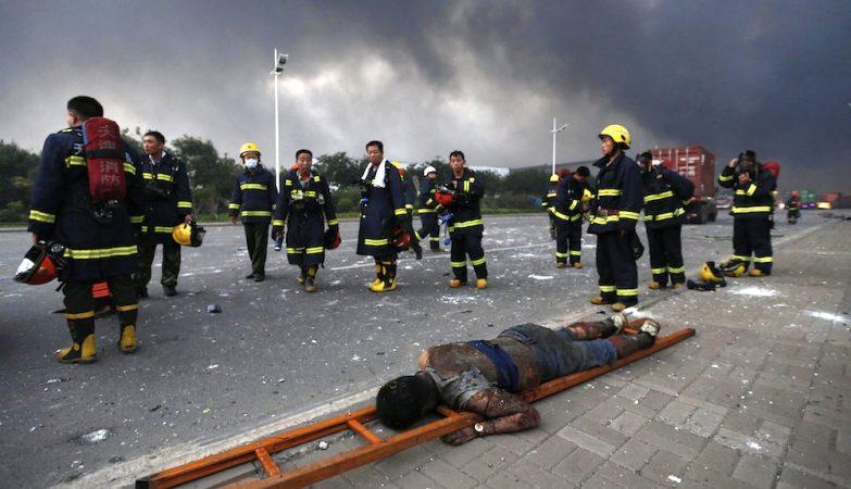 Bombeiros junto ao corpo de uma das vítimas das duas violentas explosões de Tianjin, na China