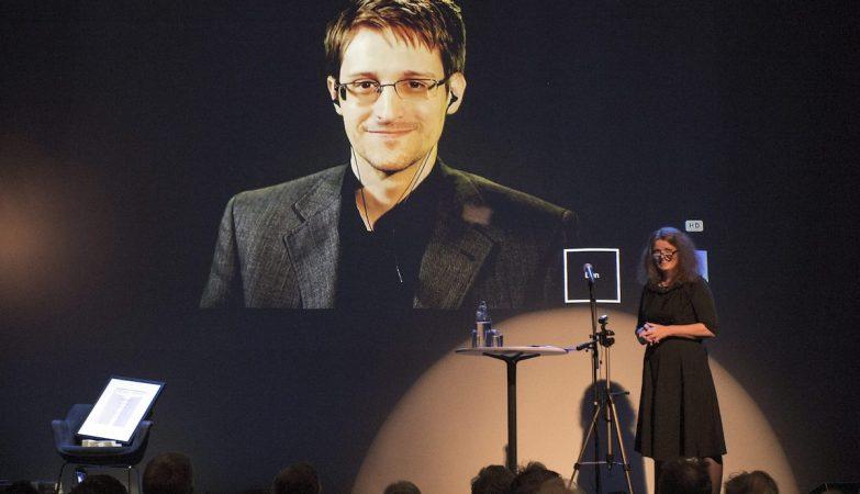 A presidente da Academia Norueguesa de Literatura, Hege Newth Nouri (dir), entrega o  Bjornson Prize 2015 a Edward Snowden (no ecran),em cerimónia que decorreu em Molde, na Noruega