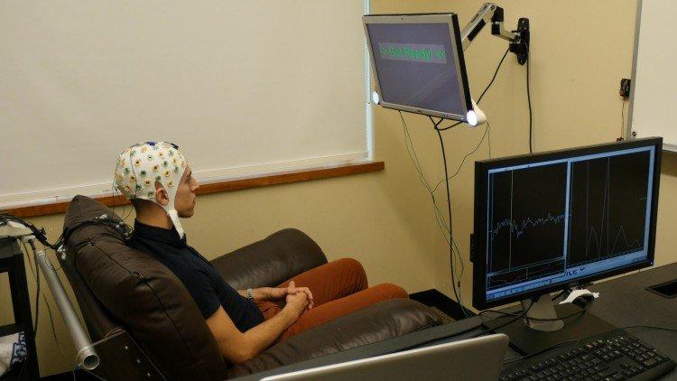 Um estudante usa o capacete de eletroencefalografia (EEG) que regista a atividade cerebral e envia uma resposta para outro participante pela Internet