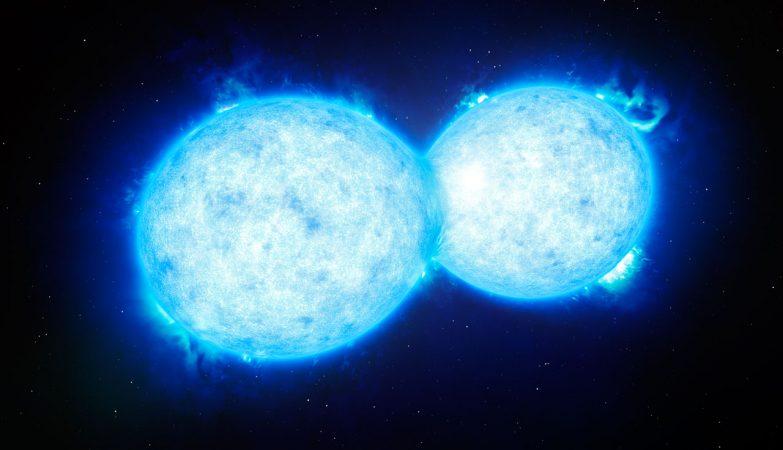Esta impressão artística mostra VFTS 352 — o sistema binário mais quente e mais massivo descoberto até à data, onde as duas componentes estão em contato, partilhando material. As duas estrelas deste sistema extremo, que se situa a cerca de 160.000 anos-luz de distância na Grande Nuvem de Magalhães, podem estar a dirigir-se para um final dramático, no qual fusionam para formar uma única estrela gigante ou então dão origem um buraco negro binário.