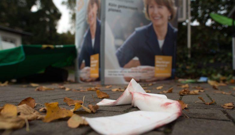 Ligaduras usadas para prestar osprimeiros socorros após o ataque a Henriette Reker, deixadas para trás no local, em frente a outdoors com a figura da candidata