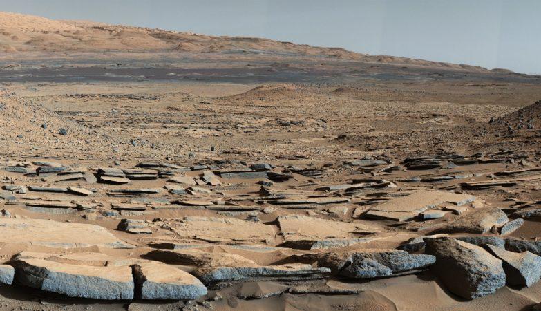 """Formação """"Kimberley"""", em Marte, captada pelo rover Curiosity da NASA. Os estratos no plano da frente inclinam-se para a base do Monte Sharp, indicando um fluxo de água em direção a uma bacia que aí existiu antes da constituição da maior parte da montanha"""