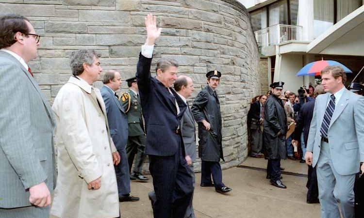 O presidente Ronald Reagan acena aos jornalistas à saída do Hotel Hilton. À esquerda, de gabardina branca, o agente Jerry Parr.