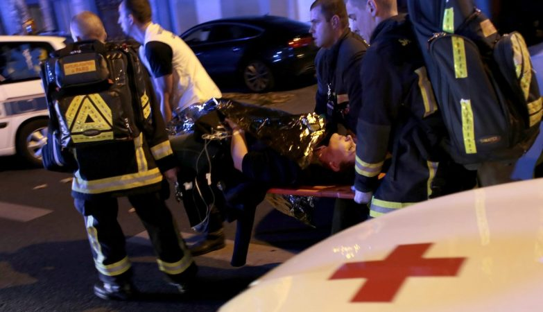 Paramédicos transportam uma mulher ferida após os atentados em Paris