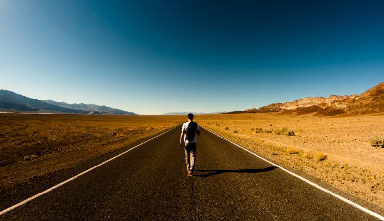 Um homem e uma estrada no deserto
