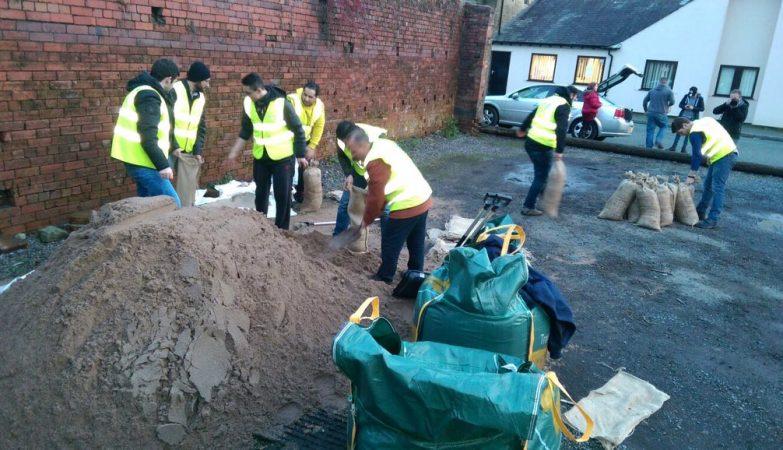 Refugiados sírios ajudam a encher sacos de areia em Rochdale, no Reino Unido