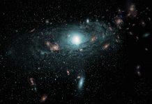"""Impressão de artista das galáxias descobertas na """"Zona de Evitamento"""" por trás da Via Láctea. Esta cena foi criada usando dados posicionais verdadeiros das novas galáxias e povoando aleatoriamente a região com galáxias de tamanhos, tipos e cores diferentes."""