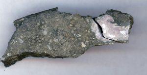 Ampliação de uma inclusão cerâmica refratária ainda embebida no meteorito (rosa). As inclusões refratárias são as rochas mais antigas conhecidas no Sistema Solar (4,5 mil milhões de anos). A análise dos rácios dos isótopos de urânio destas inclusões demonstra que um isótopo de longa vida do elemento cúrio radioativo estava presente no Sistema Solar quando esta inclusão foi formada