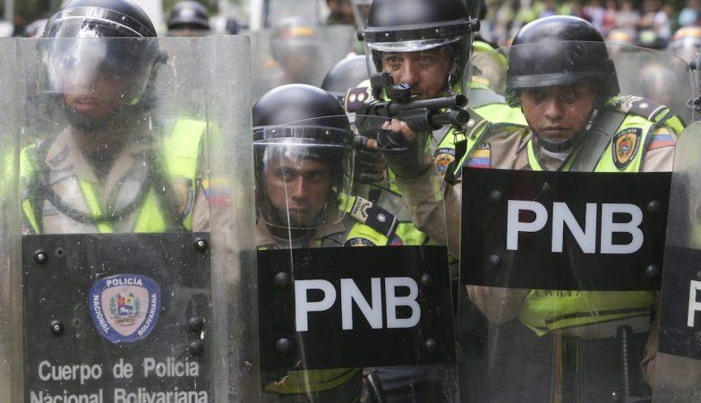 Agentes da Polícia Nacional Bolivariana em formação contra opositores em protestos pelo referendo na Venezuela