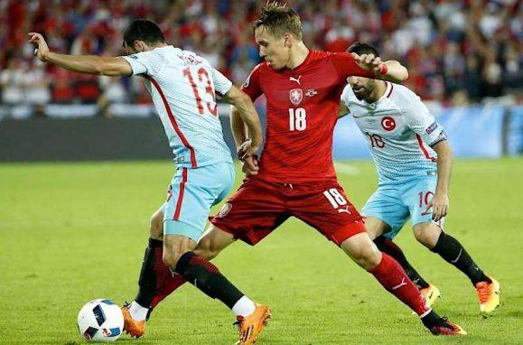 O turco Ismail Koybasi (esq) e o checo Josef Sural (c) num lance do Turquia 2-0 República Checa
