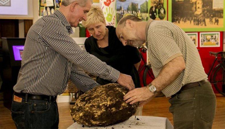 Funcionários de Museu irlandês com pedaço de manteiga de 2 mil anos desenterrado de um pântano.