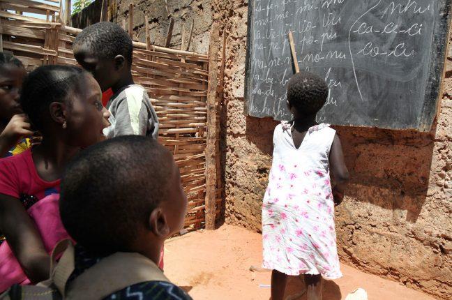 Vilma na escola que fica debaixo de uma árvore no Bairro Militar em Bissau. Vilma escapou a quatro tentativas de homicídio por ser considerada uma criança irã, devido a uma deficiência na locomoção e convulsões não diagnosticadas.