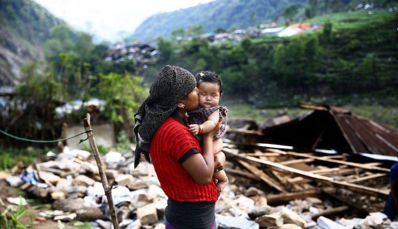 Uma nepalesa beija a filha em frente aos escombros da sua casa, em Baluwa, Nepal, depois do terremoto em 2015