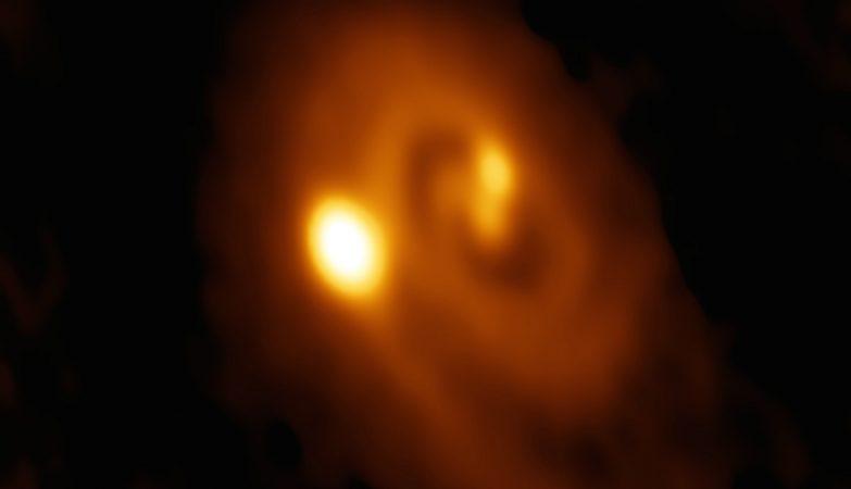 Imagem ALMA do sistema L1448 IRS3B, com duas jovens estrelas no seu centro e uma terceira distante delas. A estrutura espiral no disco de poeira em seu redor indica instabilidade.