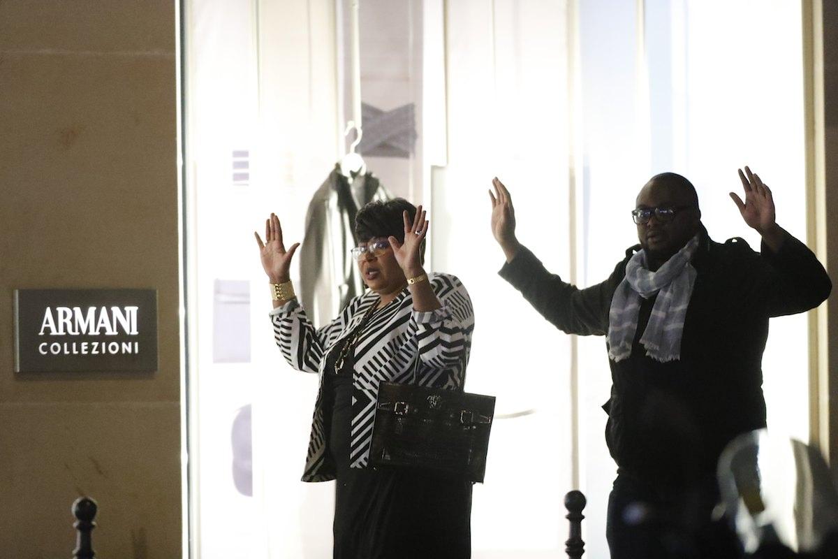 Dois cidadãos parisienses levantam os braços ao ouvir tiros durante o ataque que vitimou dois agentes da polícia nos Campos Elísios