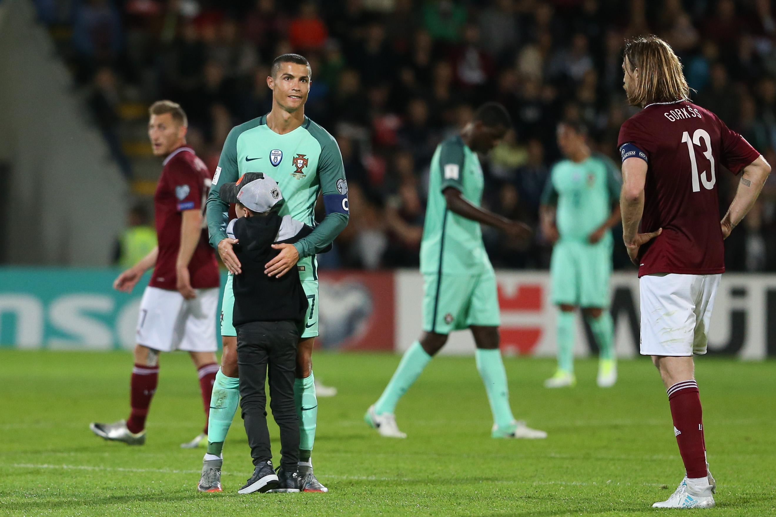 Uma criança foge aos seguranças e abraça Cristiano Ronaldo no fim do jogo com a Letónia