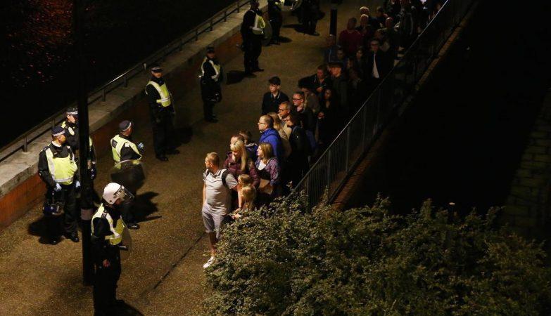 Agentes da Polícia Metropolitana de Londres com pessoas evacuadas da London Bridge após o atentado