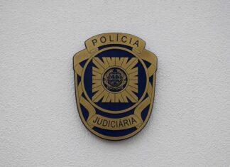 Crachá da Polícia Judiciária (PJ) numa parede